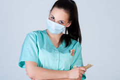 Nurse or doctor wearing  mask and holding money Royalty Free Stock Image