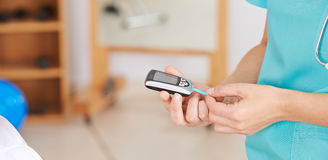 Nurse doing blood glucose monitoring. With diagnostic medical dipstick Stock Image