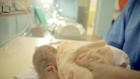 Nurse dress just born child in a new clothes. Nurse dress just born child in a new warm clothes in a nursery on a white table stock footage