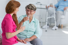 Nurse drinking water with senior woman Royalty Free Stock Photos