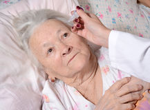 Nurse dripping eye drops to old woman Royalty Free Stock Photo