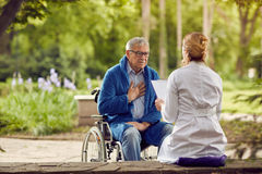 Nurse with elderly man in wheelchair who don`t feel good. Nurse with elderly men in wheelchair who don`t feel good outdoor Royalty Free Stock Photos