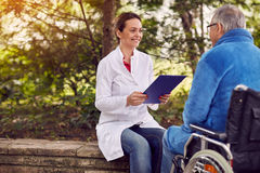 Nurse with elderly man disabled in wheelchair. Nurse with elderly men disabled in wheelchair outdoor Royalty Free Stock Photos