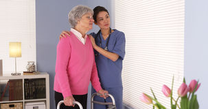 Nurse and elderly patient standing by window looking out Stock Images
