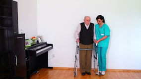 Nurse and Elderly Senior Man Using Walking Frame Stock Photo