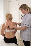 Nurse examine a patients back using a stethoscope Stock Photos