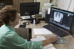 A nurse examines a radiograph of a patient on a monitor stock image