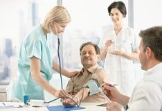 Nurse examining blood pressure for patient stock image