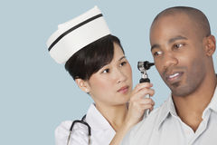 Nurse examining male patient's ear over light blue background Royalty Free Stock Photography