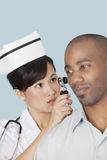 Nurse examining male patient's ear over light blue background Stock Image