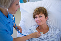 Nurse examining a patient with a stethoscope Stock Photos