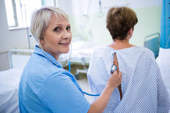 Nurse examining a patient with a stethoscope Stock Photo