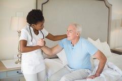 Nurse examining a senior man on bed in bedroom. Nurse examining a senior men on bed in bedroom at home Stock Photos