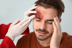 Nurse examining young man`s head injury in clinic. First aid royalty free stock image