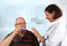 Nurse explains an inhaler to a patiënt. Hold breath for 5 seconds stock photography