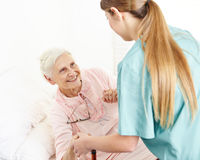 Nurse at extended home care helping. Smiling senior women out of bed Stock Images