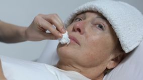 Nurse feeding crying old woman with towel on forehead, disability after illness. Stock footage stock footage