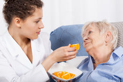 Nurse feeding an elderly woman Royalty Free Stock Images