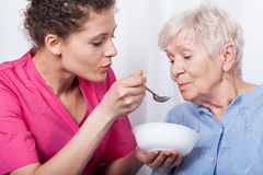 Nurse feeding an older lady Stock Images