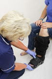 Nurse Fitting an Orthopaedic Boot to a Lady with a Broken Leg. Lady with a broken leg having an orthopaedic boot fitted by a nurse stock photo