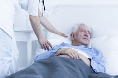 Nurse fluffing pillow of patient Royalty Free Stock Images