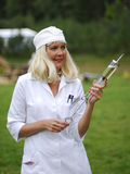 Nurse with a gigantic syringe. A view of a woman dressed as a nurse in a white uniform and cap as she walks across an open area outside, carrying a gigantic make Stock Photo