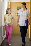 Nurse and girl holding hands and walking down corridor Stock Photo