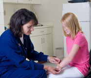 Nurse giving band aid to patient Stock Photos