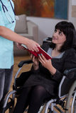Nurse giving book to disabled woman Stock Photography