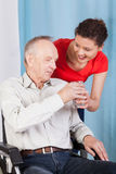 Nurse giving disabled man glass of water Royalty Free Stock Images