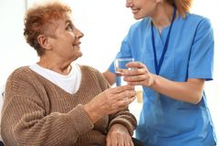 Free Nurse Giving Glass Of Water To Elderly Woman. Medical Assistance Royalty Free Stock Photos - 159960318