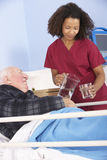 Nurse giving glass of water to senior man in hospital Stock Photo