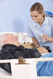 Nurse giving glass of water to senior man in hospital Stock Photos