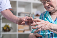 Nurse giving glass of water to senior woman Royalty Free Stock Photography