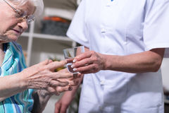 Nurse giving glass of water to senior woman Stock Photography