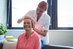 Nurse giving head massage to senior woman Royalty Free Stock Images