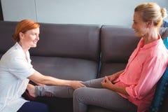 Nurse giving leg massage to senior woman Royalty Free Stock Photos
