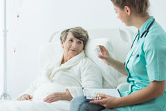 Nurse giving medcines to patient Stock Photography