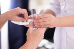 Nurse giving medication. Nurse handing her patient some water. Close up shot of glass of water being passes from hand of female doctor to her patient stock photo
