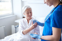 Nurse giving medicine to senior woman at hospital Royalty Free Stock Photography