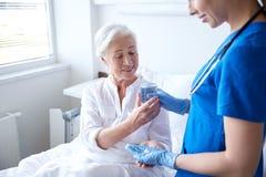Nurse giving medicine to senior woman at hospital Royalty Free Stock Photography