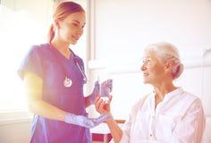 Nurse giving medicine to senior woman at hospital Royalty Free Stock Photos