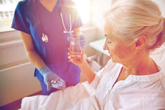 Nurse giving medicine to senior woman at hospital Royalty Free Stock Image