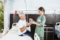 Nurse Giving Medicine And Water To Senior Patient royalty free stock photos