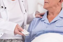 Nurse giving medicines. Close up of nurse giving medicines to ill patient Royalty Free Stock Image
