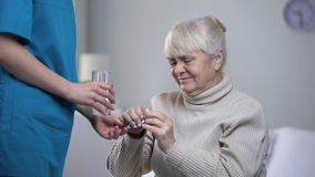 Nurse giving painkillers elderly woman suffering from headache, taking care. Stock footage stock footage
