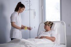 Nurse giving pills Royalty Free Stock Photos