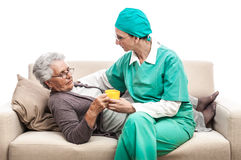 Nurse giving pills to old sick woman Stock Images