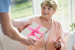 Nurse giving present to elderly woman Royalty Free Stock Image