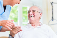 Nurse giving senior man prescription drugs Royalty Free Stock Image